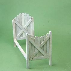 Miniature dollhouse bed of fence pickets made from wooden stir sticks.