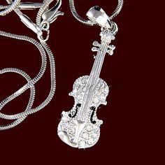 Swarovski Crystal Musical Instrument (Violin-Viola-Cello) Necklace & Pendant.  This Gorgeous Silver Rhodium Finish Violin Pendant Charm is Hand-Inlayed with Genuine Swarovski Crystals and comes with a free 16 inch snake chain necklace with lobster clasp closure.  Approximately Pendant Size: 1 Wide x 3-1/4 High or (2-1/2cm x 8cm) Necklace size: 16 (42cm) Plus 2 extender is 18 (45cm)  The pendant has a magnificent Diamond Brilliantly Simulant that Swarovski Crystals can produce. F...