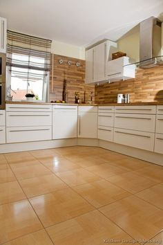 #Kitchen Idea of the Day: Modern white kitchen with warm-toned flooring.
