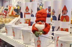 Luukku 12: Mikä kurkistaa mukista? Tonttu nauttii kaupan tuoksuista. Voi aavistaa joulun lähestyvän, hyllyistä maakuntamuseon myymälän. Löytyy lahjoja isoille ja pienille, tämä vinkkinä kaikille tontuille.
