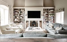 Living Room, TV, upholstered buttoned footstool, sofas, curtains, roman blinds, fireplace, book shelves, logs, wall lights, floor lamps