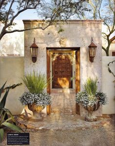 I like the double entry, I picture the door opening into a courtyard with a fountain. French urns flank entry to Spanish-style courtyard; Palm Design Group.