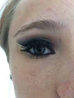 Black smokey eye with blended cut crease, extended inner corner with lines water line and a gold outside edge.