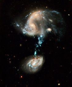 """""""Fountain of Youth"""" Arp 194: interacting galaxies, along with a """"cosmic fountain"""" of stars, gas, & dust that stretches over 100,000 light-years. The northern part appears a haphazard collection of dusty spiral arms, bright blue star-forming regions, >2 galaxy nuclei that appear to be connected & in the early stages of merging. A 3rd, relatively normal, spiral galaxy appears off to the right. The southern part contains a single large spiral galaxy with its own blue star-forming regions."""