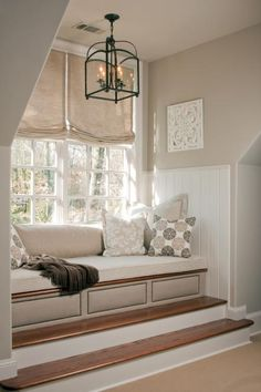 To bring an interesting focal point to the guest bedroom, Pineapple House designers made a window seat and/or daybed in an oversized dormer window. The windows were so high that steps were added for access to the perch. Panels across the bottom of the built-in are created via thumbtacks into the upholstered base.