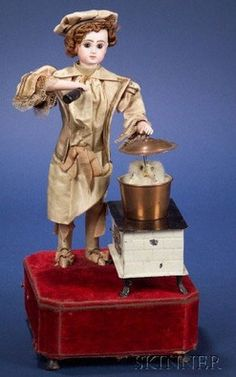 Rare Roullet et Decamps automaton of a Chef and Cat, standing by a painted tin stove, one bisque hand brandishing a wine bottle, the other resting on the lid of a copper pot, on velvet-covered base with going-barrel