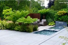 Creating a Tropical Garden in a UK Climate: this has cool, tropical feel, despite there being traditional English trees and shrubs behind it; this green backdrop showcases exotic (but not necessarily tropical) plants within the garden itself. Darker wood (ipe) helps the tropical look. | Garden Arts via houzz
