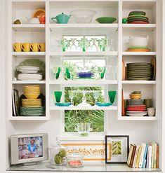 Cabinets often frame windows, but in this kitchen, shelves span the opening, which backlights the green and turquoise glasses.
