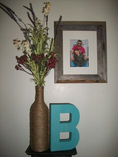 My homemade jute-wrapped wine bottle with flower details, a painted B, and a photo frame on wall. Ideas for wedding