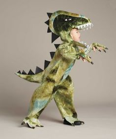"""Colossal T. Rex Costume For Boys - exclusively ours - Travel back in time to when humongous dinosaurs roamed the Earth. Your awesome T. rex is costumed in a soft patterned bodysuit with """"scales,"""" a long tail and attached shoecovers."""