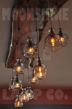 Made for a lake house in Washington, this beautiful wood chandelier is made from a piece of live edge eucaplytus and 12 hand cut Patron Tequila bottles.