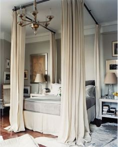 Curtain rods hung from the ceiling to simulate a canopy bed. This I love.