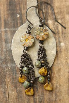 Little 8mm opaque yellow Picasso petals dangle from lengths of copper chain alongside 6mm faceted green bronze beads. The focal is a 12mm