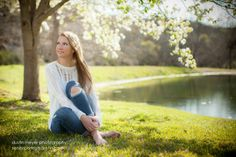 A blonde teen female in white shirt and blue jeans poses by a pond for her senior portraits. | Yelp