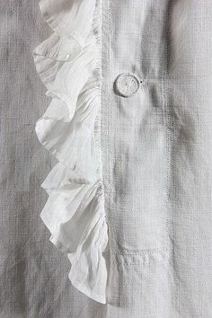 Detail of shirt front of a gentleman's voluminous nightshirt of fine white linen with ruffle edging to collar, neck opening and cuffs. mid 18thC