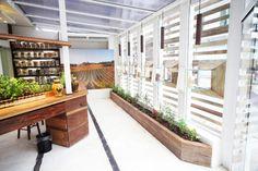Artgusto loja e fabrica de massa fresca. Detalhe da vetrine e das hortas em madeira de demoliçao, piso em cimento queimado com listras de aço carbono cortain.