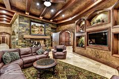 Traditional Living Room with Tillandsia Cyanea Air Plant on Grapewood Branch, High ceiling, Exposed beam, stone fireplace