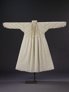 A woman's fine linen smock of the early 17th century is trimmed and inset with bobbin lace arranged in a distinctive diagonal pattern. The lace insertions are of the same design, but two different qualities, one finer than the other. Clearly there was not enough of the fine lace to complete the garment, so the coarser variety was used in alternate rows. This may have resulted as a miscalculation of how much lace to buy or because the cost of the finer, more expensive lace was too great.