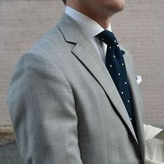 Light grey plaid suit, white shirt, navy knit tie with white polka dots