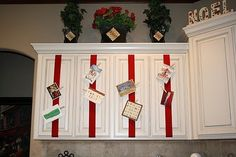 Run a piece of ribbon down the front of your cabinet doors and attach Christmas cards with clothespins.  Such a great idea!