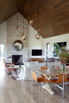 Living room-dining room and kitchen with wooden V-shaped ceiling