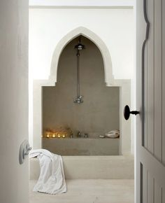 Moroccan style bathroom with gray door opening to reveal tadelakt plastered walls, floors and Moorish arched tub alcove filled with traditional shower head and faucet. House Design, Moroccan Interiors, Interior, Home, Bathroom Styling, House Interior, Interior Design, Beautiful Bathrooms, Bathroom Inspiration