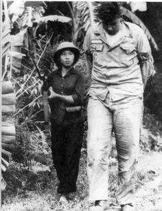 American Airman Bill Robinson being guarded by an NVA soldier following his capture on September 20, 1965; his helicopter was shot down and the crew was taken to the Hanoi Hilton.  He became the longest-held POW in American history after spending more than seven years in captivity - he was released from the Hanoi Hilton in February of 1973.