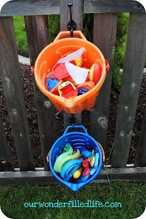 Hang buckets up on the fence to store toys on your preschool playground. Great idea for kids that love to be outdoors and a great way to make it so toys dont go missing. Preschool Playground, Backyard Playground, Backyard For Kids, Backyard Projects, Outdoor Projects, Backyard Toys, Playground Ideas, Pool Toy Storage, Outdoor Toy Storage