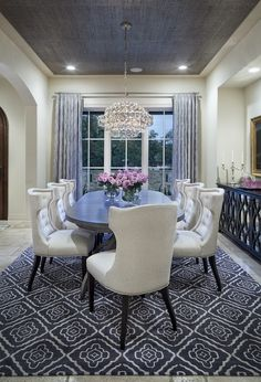 cream-colored dining room with grey rug, curtains and ceiling