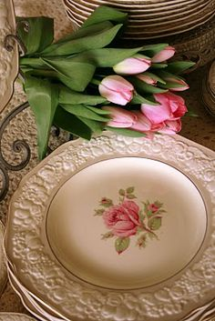 Beautiful rose patterned plates and pink tulips.