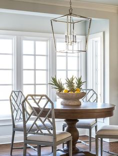A Darlana Lantern lights a round wood dining table surrounded by dove gray bamboo dining chairs placed in front of windows in a chic breakfast nook.