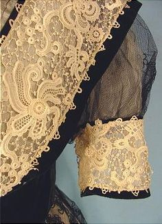 close-up detail of a 1907 evening gown of black embroidered and appliqued lace with ecru Venise lace