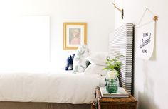 White walls, striped headboard, white bedding, printed blue and grey throw pillows, and basket woven nightstand