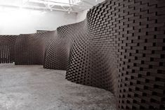 Photo of a brick wall with oscillating pattern.