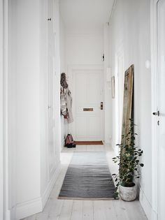 Narrow white hallway in a Swedish apartment...