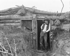 Cowboy in a sod dugout, common to pioneer settlers as they constructed homestead cabins.