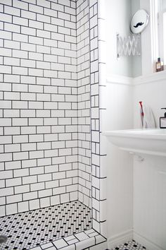 Hope this is what we could do after we remove our ugly acrylic tub. Fantastic tile job - white tiles, black grout.  From: Eric's Stylish, Sunshine-Filled House; Apartment Therapy