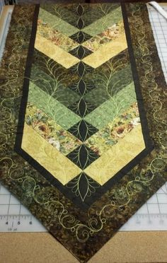 I particularly like the swirl border design on this tablerunner by Wendy in Arizona. Webpage shows some more details.