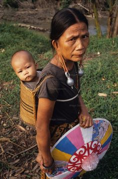 DAYAK, MALAYSIA. Sarawak, Borneo, South East Asia. Dayak, 'Kenyah', woman and child in papoose.