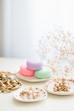 Acessórios dourados, macarrons (lipbalm com embalagem em formato de macaron) e pratinhos branco com detalhes dourados e flores.