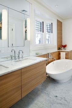 Contemporary #bathroom design with wood cabinets, freestanding tub, and #marble countertops and #tile.