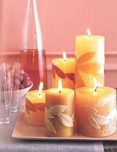 Pillar candles embellished with graceful wax impressions of leaves autumn fall events parties weddings