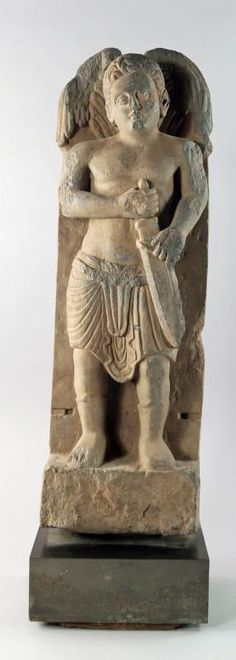 A large grey schist figure, probably depicting Thanatos, Greco-Gandhara, 2nd/3rd century, modelled in the round, standing full length with detailed hair, with large wings and carrying short sword, raised upon rectangular plinth, from a larger architectural fixture, 67cm high - Price Estimate: £1000 - £1500