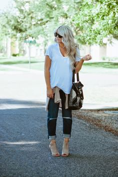 oversized white tee [messy tuck], tan sweater wrapped around the waist, dark wash ripped boyfriend jeans, tan peep toe booties.