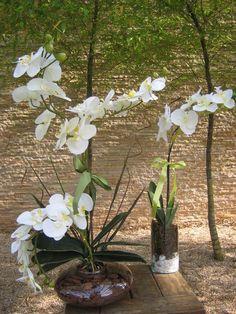 Lindo conjunto de orquideas brancas com miolo amarelo composto por:  - 1 vaso vidro oval ekebana com 3 orquídeas,cascalho,folhagens e rococo - medidas do vaso: 20 cma.larg. altura total com arranjo65 cm.  -1 vaso redondo com pedrinhas brancas e musgos com 1 orquidea branca e folhagens, e rococó medidas do vidro: 12x25 cm. altura total com arranjo 60cm.  Faço com orquídeas de diversas cores como por exemplo: vermelha,turquesa,branca com miolo pink,laranja,roxo,lilás,pink,rosa  Voce monta…