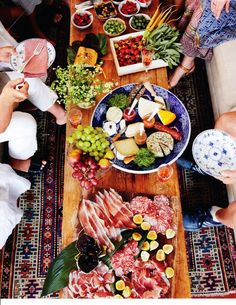 An Epic Spread Of Meats & Cheeses In The Summer. Dried meats as far as the eye can see. A giant bowl of cheese. Olives and fruits spreading into the distance.