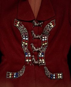 Brown wool tailored jacket with coloured metal and glass beaded appliques on the front, large cold-painted cast-metal alloy buttons down the front in the form of circus horses. Concealed pockets behind appliques.