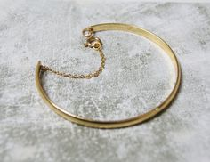 A timeless gold plated simple bangle. The bracelet width is 7mm with a gold plated fastening chain for a classic and elegant look. Perfect for