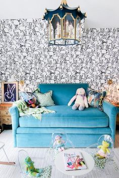 A blue pagoda lantern hangs over a Saarinen play table surrounded by Lou Lou Ghost Chairs placed on a light gray rug in front of a blue velvet daybed flanked by French wood nightstands lit by brass and glass sconces mounted on a wall covered in black and white Groundworks Hutch Wallpaper.