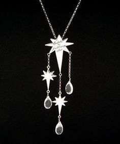 """This unusual silver necklace looks stunning dressed up or down. The large star is hand engraved with the message 'catch a falling star' and oxidised for extra impact. Two further small stars and three briolette quartz crystals are suspended below for extra sparkle. Large star measures 4cm long by 3cm wide, small stars measure 2.5cm long by 1.75 cm wide. Necklace chain is 16"""" and the total drop length section is 10.5 cm. Matching earrings are available. All jewellery comes in a Kat Zahran…"""